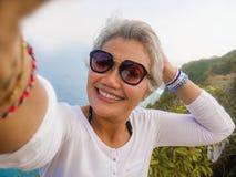 中年有采取与手机的灰色头发的50s愉快和快乐的亚裔妇女selfie在美丽的热带海滩海岛 库存图片