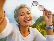 中年有采取与手机的灰色头发的50s愉快和快乐的亚裔妇女selfie在美丽的热带海滩海岛 图库摄影