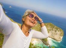 中年有采取与手机的灰色头发的50s愉快和快乐的亚裔妇女selfie在美丽的热带海滩海岛 库存照片