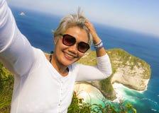 中年有采取与手机的灰色头发的50s愉快和快乐的亚裔妇女selfie在美丽的热带海滩海岛 免版税库存图片