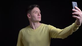 中年白种人人画象做selfie照片的黄色毛线衣的使用智能手机在黑背景 股票视频