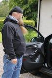 中年的人,与长的胡子在一个开放车门前疑惑地站立 免版税库存照片