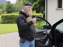中年的人,与长的胡子在一个开放车门前疑惑地站立 免版税图库摄影