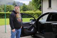 中年的人,与长的胡子在一个开放车门前疑惑地站立 免版税库存图片