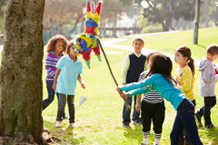 击中彩饰陶罐的孩子在生日聚会 库存图片