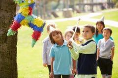 击中彩饰陶罐的孩子在生日聚会 免版税库存图片