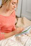 年轻中意的妇女在她的草图书写 库存图片