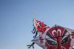 中文报纸风筝行飞行在清楚的蓝天的 免版税库存照片