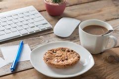 中断咖啡办公室 一张木桌用巧克力曲奇饼 免版税库存照片