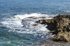 中断在一个石海滩的通知,形成浪花 挥动并且飞溅在海滩 失败在岩石上挥动 库存照片