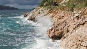 中断在一个石海滩的通知,形成浪花 英尺长度 飞溅在海的岩石挥动 免版税库存图片