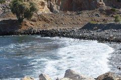 中断在一个石海滩的通知,形成浪花 免版税库存图片