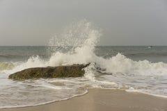 中断在一个石海滩的通知,形成浪花 库存照片