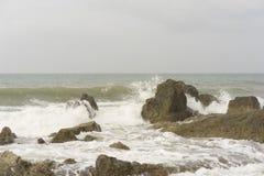 中断在一个石海滩的通知,形成浪花 免版税库存照片