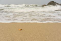 中断在一个石海滩的通知,形成浪花 库存图片