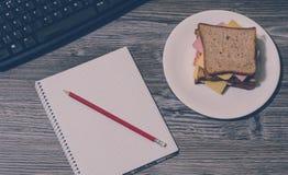 中断工作 在一支板材、笔记本和红色铅笔的火腿和乳酪三明治有在灰色木背景的键盘的 葡萄酒作用 免版税库存图片