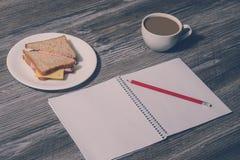 中断工作 打开习字簿用在一块白色板材的一个铅笔、火腿和乳酪三明治,杯子在木背景的热的茶 葡萄酒 库存图片