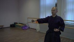 中景,主要kendo在鞘把从鞘和棍子的katan ` s剑向后拉它 股票视频