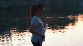中景,美丽的女孩由桨漂浮在一口的身分和行 股票视频