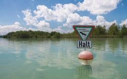中止,止步不前标志为在德语的自然保护风景警告,采取从皮船 水厂、芦苇和海岛Wörth 免版税库存图片