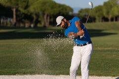 击中沙子地堡射击的前高尔夫球运动员 图库摄影