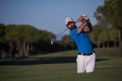 击中沙子地堡射击的前高尔夫球运动员 免版税图库摄影