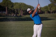 击中沙子地堡射击的前高尔夫球运动员 库存照片