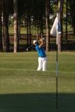 击中沙子地堡射击的前高尔夫球运动员 免版税库存图片