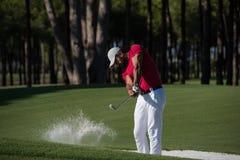 击中沙子地堡射击的高尔夫球运动员 免版税库存照片