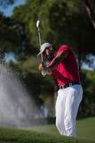 击中沙子地堡射击的高尔夫球运动员 库存图片