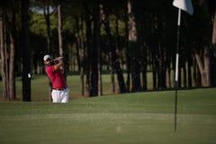 击中沙子地堡射击的高尔夫球运动员 免版税库存图片
