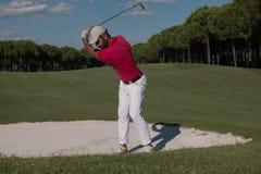 击中沙子地堡射击的高尔夫球运动员 库存照片