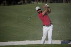击中沙子地堡射击的高尔夫球运动员 免版税图库摄影