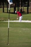 击中沙子地堡射击的高尔夫球运动员 图库摄影