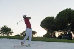 击中沙子地堡的高尔夫球运动员在日落射击了 库存图片