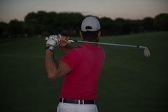 击中沙子地堡的高尔夫球运动员在日落射击了 库存照片