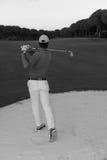 击中沙子地堡的高尔夫球运动员在日落射击了 免版税库存图片