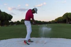 击中沙子地堡的高尔夫球运动员在日落射击了 免版税库存照片