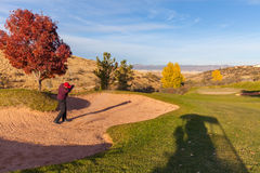 击中沙子射击的高尔夫球运动员 免版税库存照片