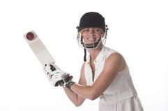 击中球的女性玩板球者 库存照片