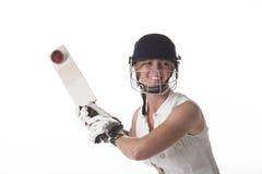 击中球的安全帽的女性玩板球者 免版税库存照片