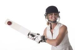 击中球的安全帽的女性玩板球者 库存照片