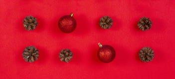 中看不中用的物品蓝色圣诞节构成玻璃 样式由杉木锥体和红色圣诞节装饰制成在红色背景 顶视图,平的位置 免版税图库摄影