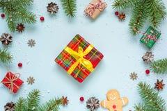 中看不中用的物品蓝色圣诞节构成玻璃 框架由杉树、装饰、红色莓果、礼物盒和杉木锥体做成 库存图片