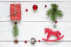 中看不中用的物品蓝色圣诞节构成玻璃 框架由圣诞节礼物,杉木锥体,杉树制成分支,红色球、莓果和玩具马 免版税库存图片