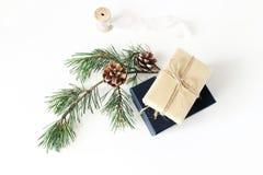 中看不中用的物品蓝色圣诞节构成玻璃 有杉木分支与锥体和丝绸丝带的欢乐被包裹的圣诞礼物箱子在白色桌上 库存照片