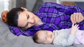 中等享受母性的特写镜头愉快的年轻女人说谎与在床上的一点可爱宝贝 股票录像