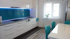 中等大小厨房公寓,皮革现代和最低纲领派seater,六个人的白色餐桌照片在绿松石颜色的 库存照片