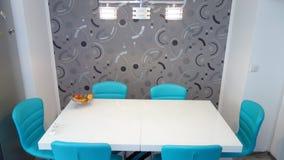 中等大小厨房公寓,皮革现代和最低纲领派seater,六个人的白色餐桌照片在绿松石颜色的 免版税库存照片