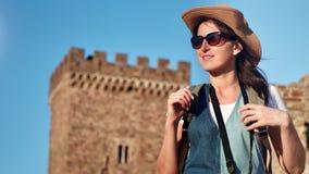中等帽子和太阳镜的特写镜头可爱的微笑的年轻旅行妇女享受日落的室外 股票录像